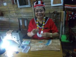 Diese fröhliche Frau verziert Baumrindenstoff