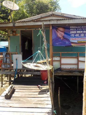 Eines der Häuser mit Wahlwerbung und Fisch zum Trocknen